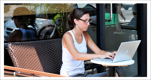 woman typing on a laptop at a coffee shop